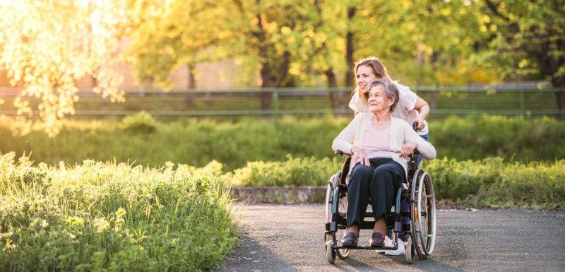 Grand-mère dans un fauteuil roulant se promenant avec sa fille au printemps